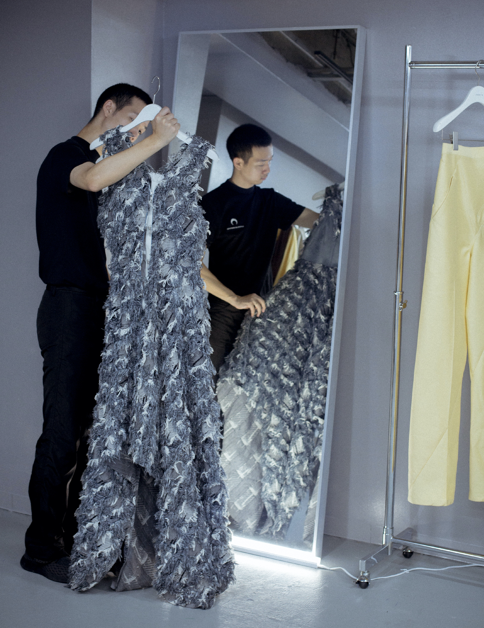 designer looking at his dress in the mirror
